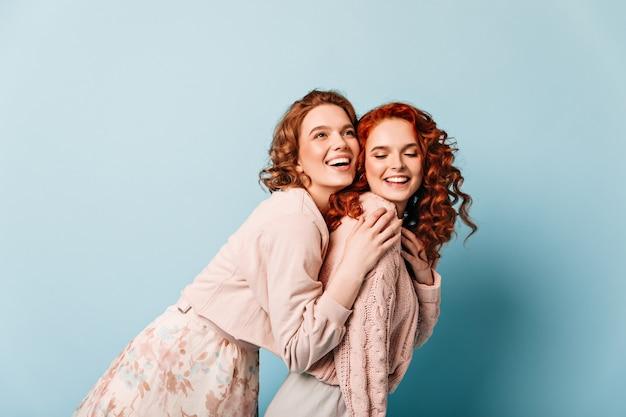 Glückseliges mädchen, das ingwerfreund umarmt. studioaufnahme von zwei reizenden damen, die auf blauem hintergrund aufwerfen.