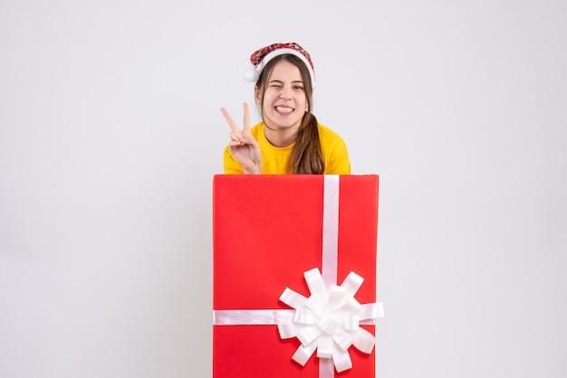 Glückseliges mädchen der vorderansicht mit der weihnachtsmütze, die siegeszeichen macht, das hinter großem weihnachtsgeschenk steht