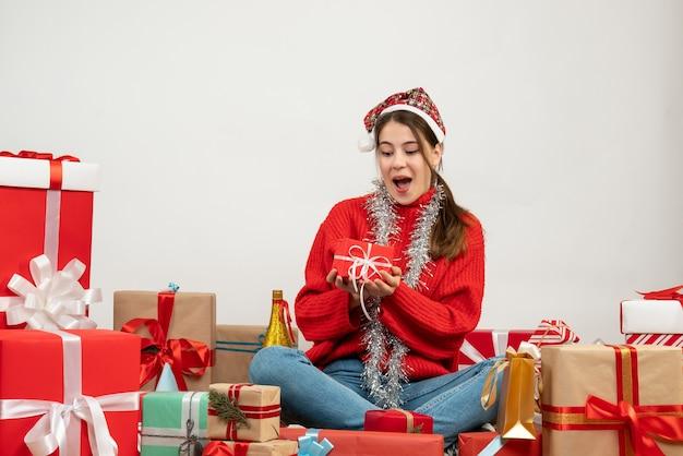Glückseliges mädchen der vorderansicht mit weihnachtsmütze, die geschenk hält, das um geschenke sitzt