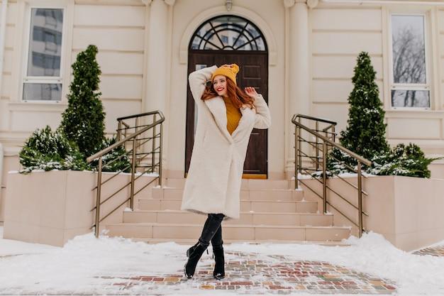 Glückseliges mädchen im weißen kittel, das positive gefühle im winter ausdrückt. außenaufnahme der reizenden kaukasischen frau, die im januar aufwirft.