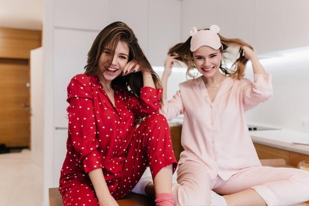 Glückseliges mädchen in der rosa nachtwäsche, die mit gefalteten beinen sitzt und lächelt. innenporträt der fröhlichen brünetten dame in den roten kleidern, die in der küche aufwerfen.