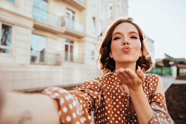 Glückseliges mädchen in der vintage-kleidung, die selfie auf der straße macht. wunderschöne kaukasische dame im braunen outfit, das luftkuss sendet