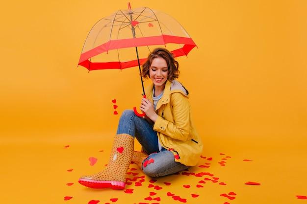 Glückseliges mädchen in gummischuhen, das mit regenschirm auf dem boden sitzt und lacht. glückliche weiße frau im herbstmantel, der valentinstag genießt.