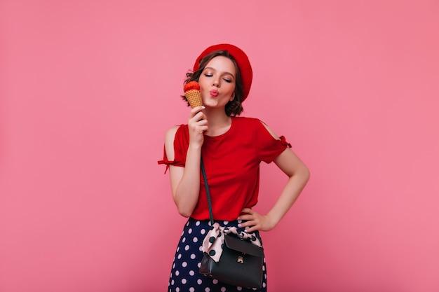 Glückseliges mädchen mit der schwarzen handtasche, die eiscreme genießt. ekstatisches weibliches modell in der baskenmütze, die mit nachtisch aufwirft.