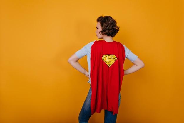 Glückseliges schlankes mädchen mit kurzem haarschnitt, das im superheldenumhang steht