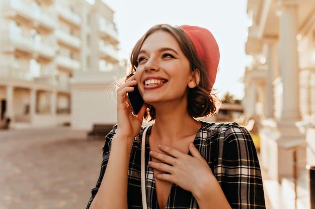 Glückseliges schönes mädchen im barett, das am telefon spricht. winsome kurzhaarige frau, die mit smartphone die straße entlang geht.