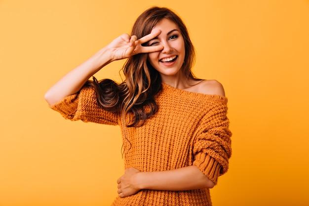 Glückseliges stilvolles mädchen, das mit friedenszeichen auf gelb aufwirft. studioporträt des gut gekleideten kaukasischen weiblichen modells, das glück ausdrückt.
