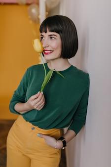 Glückseliges weißes weibliches modell im grünen pullover, der mit hand in der tasche steht. freudiges brünettes mädchen mit gelber tulpe, die zu jemandem lächelt.