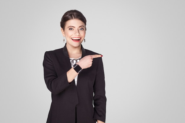 Glücksgeschäftsfrau, die mit dem finger auf den kopierraum zeigt