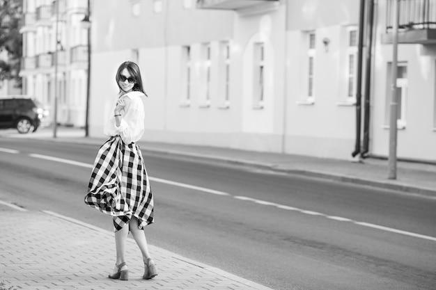 Glückskonzept - glückliche frau, die spaß auf stadtstraße hat. modefrau in sonnenbrille geht auf high heels auf der straße. schwarzweiss-bild