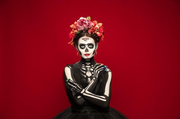 Glücksspiel. junges mädchen wie santa muerte saint death oder sugar skull mit hellem make-up. porträt auf rotem studiohintergrund mit exemplar isoliert. feiern von halloween oder tag der toten.