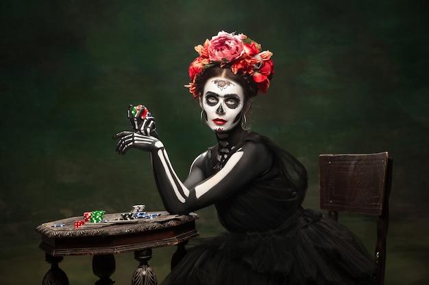 Glücksspiel. junges mädchen wie santa muerte saint death oder sugar skull mit hellem make-up. porträt lokalisiert auf dunkelgrünem studiohintergrund mit exemplar. feiern von halloween oder tag der toten.
