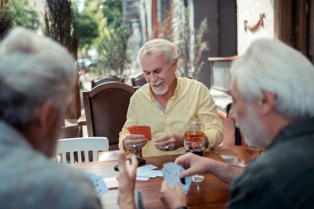 Glücksspiel mit freunden. bärtiger mann mit ringen, der abends mit freunden spielt