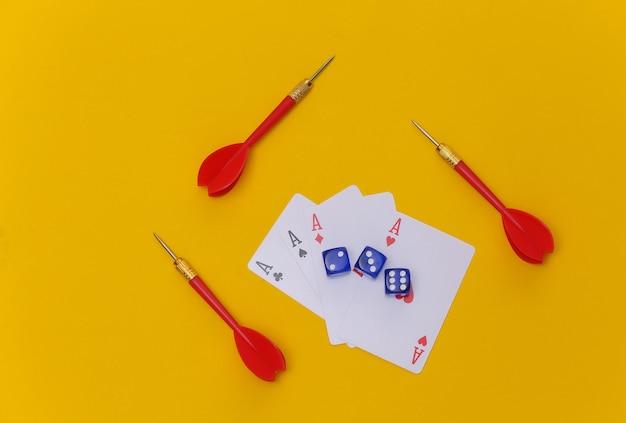 Glücksspiel. vier asse, würfel und darts auf gelbem hintergrund. ansicht von oben
