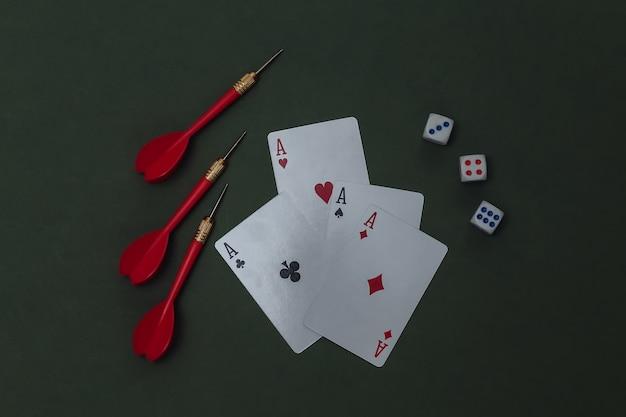 Glücksspiel. vier asse, würfel und pfeile auf grünem hintergrund.