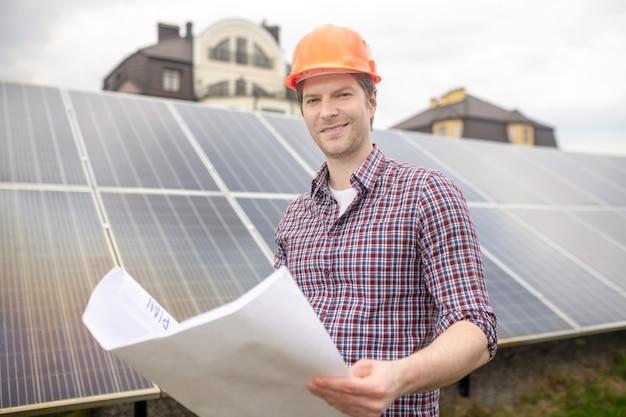 Glückstag. fröhlicher junger mann in hellem schutzhelm mit papierzeichnung auf dem territorium von landhäusern in der nähe von sonnenkollektoren