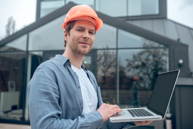 Glückstag. fröhlicher selbstbewusster lächelnder junger erwachsener mann im schutzhelm, der an einem laptop in der nähe des neu gebauten hauses arbeitet