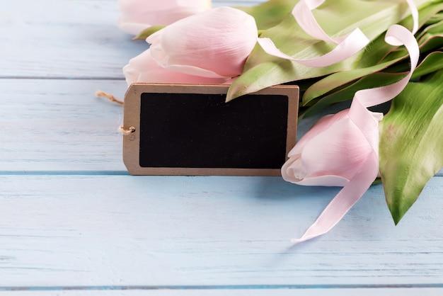 Glückwunsch-feiertagskarte mit frischer zarter rosa tulpenblume und -tafel für nachricht auf einem pastellblauen hölzernen hintergrund.