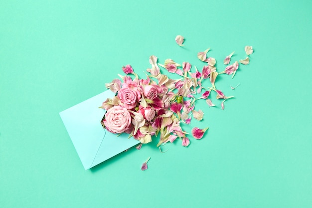 Glückwunschkarte mit handwerklichem umschlag mit frischen rosen und blütenblättern auf einem türkisfarbenen hintergrund, kopienraum. draufsicht.