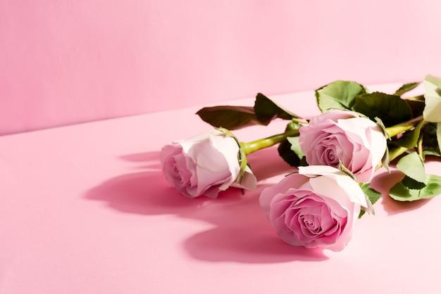 Glückwunschkomposition aus einem strauß schöner natürlicher rosenblumen an einer pastellrosa ecke