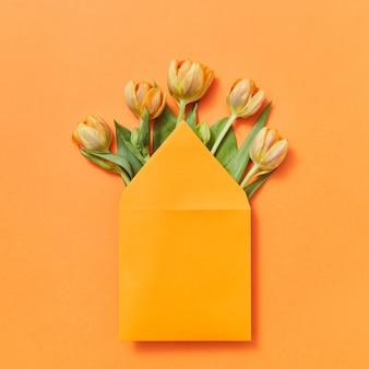 Glückwunschpostkarte des handgefertigten umschlags der gelben tulpen auf einem orangefarbenen hintergrund mit spitze für text. flach liegen.