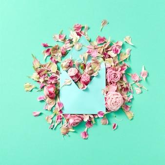 Glückwunschzusammensetzung des handgemachten umschlags und der rosa rosenblumen auf einem hellen türkisfarbenen hintergrund mit kopienraum. flach liegen.