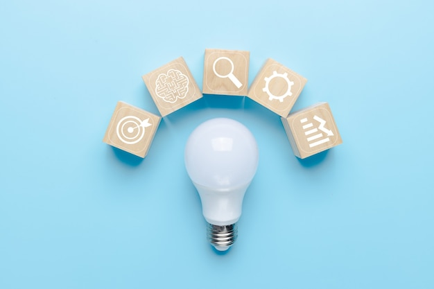 Glühbirne auf blauem hintergrund mit symbolen für brainstorming und geschäftsquellen symbol, innovation und kreatives konzept