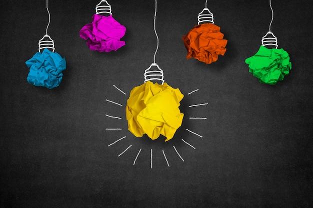 Glühbirne aus einem gelben papierkugel und andere kugeln um