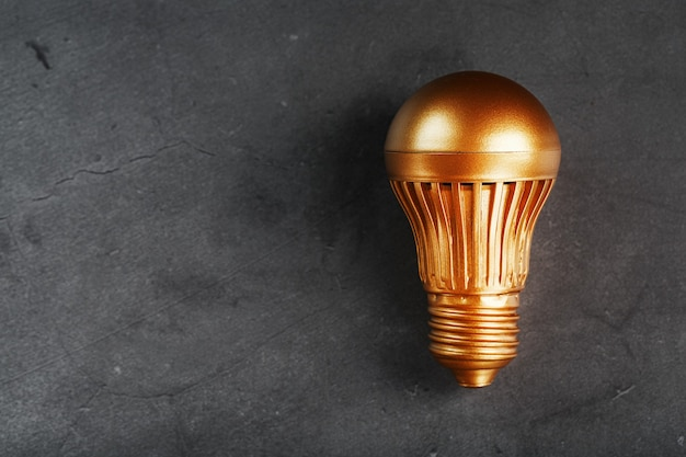 Glühbirne aus gold auf schwarzem stein