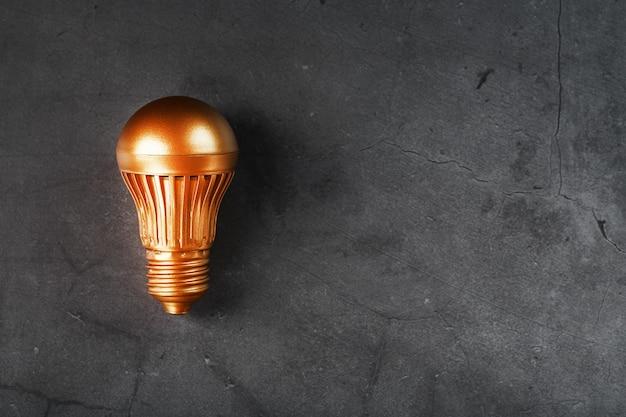 Glühbirne aus gold auf schwarzem steinkonzept einer gewinnbringenden idee
