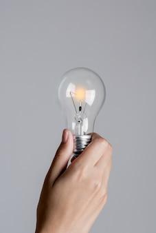 Glühbirne beginnt allmählich in frauenhand einzuschalten