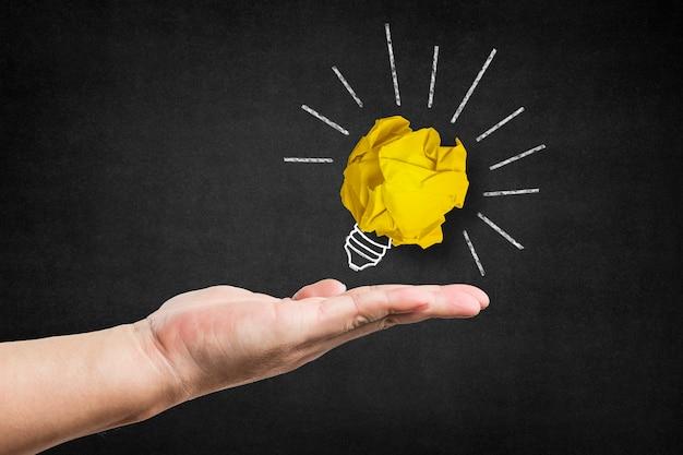 Glühbirne mit einem gelben papierkugel