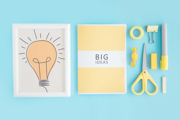 Glühbirne rahmen; großes ideenbuch und -briefpapier auf blauem hintergrund
