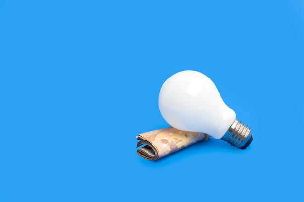 Glühbirne über einer rolle euro-scheine auf blauem hintergrund