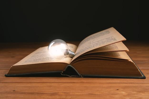 Glühbirne und buch auf dem tisch neue ideen