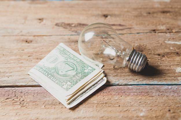 Glühbirne und geld auf einem holztisch