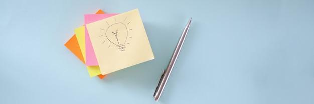 Glühbirne zeichnet auf ein stück papier viele bunte aufkleber und kugelschreiber, die auf tisch liegen