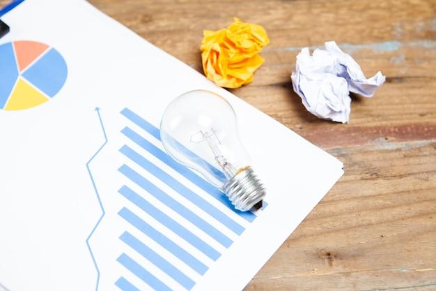 Glühbirne, zerknitterte papiere und diagramm.
