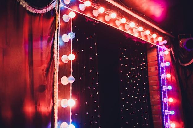 Glühbirnen auf der bühne theaterszene mit farbigen glitzer-neonröhren zur präsentation oder konzertaufführung. nachtshow am festlichen abend.
