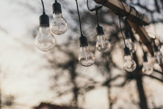 Glühbirnen auf der straße bei tageslicht. eine girlande von glühlampen auf einem hölzernen sockel am nachmittag in der sonne im freien