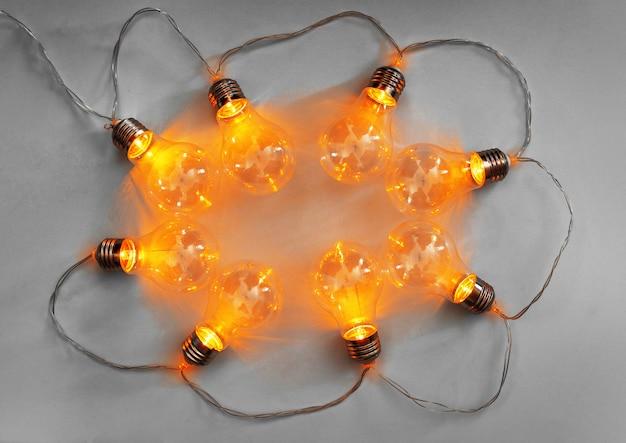 Glühbirnen beleuchteten girlande auf hellgrauer oberfläche