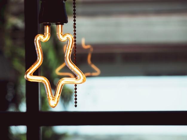 Glühbirnendekoration in sternform im café. led-lampe im retro-stil, die in der nähe des glasfensters mit kopierraum leuchtet.