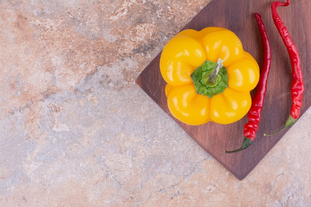 Glühende chilis mit gelbem paprika auf einem holzbrett.