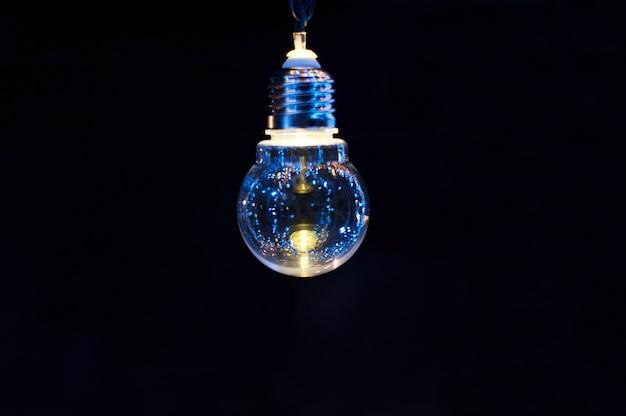 Glühende dekorative glühlampe auf einem dunklen hintergrund