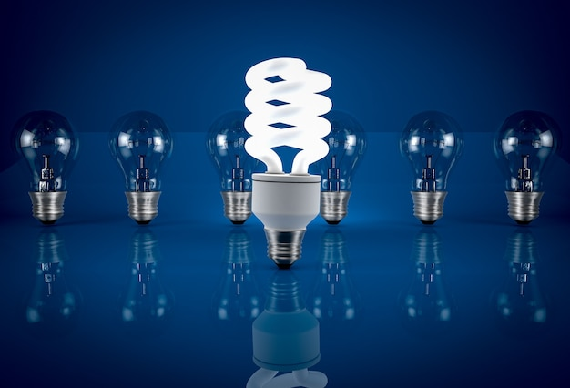 Glühende energiesparlampe unter glühbirnen auf blauem hintergrund. konzept der energieeinsparung