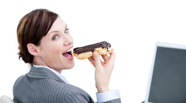 Glühende geschäftsfrau, die einen schokolade eclair isst