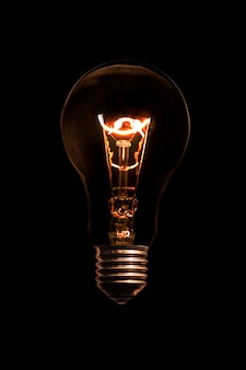 Glühende glühlampe ohne drähte auf schwarzem