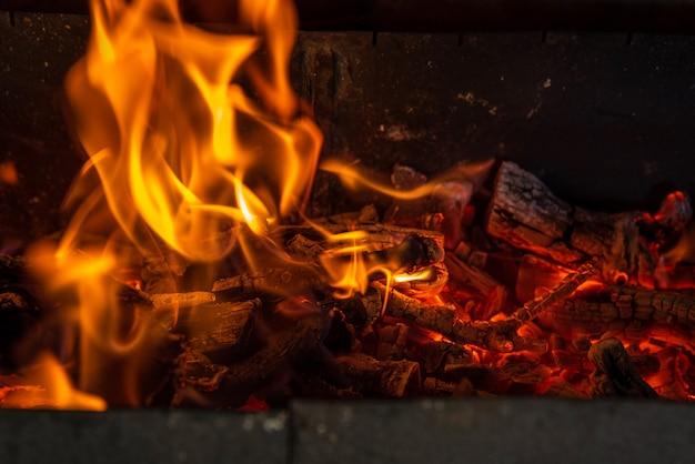 Glühende glut in heißer roter farbe. die heiße glut des brennenden holzfeuers. brennholz brennt auf grill. abstrakter hintergrund.