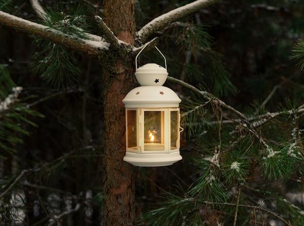 Glühende kerze in der laterne, die auf tannenzweig im winterwald hängt. weihnachtsszene.