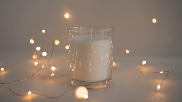 Glühende lichterkette um kerze im kerzenhalter